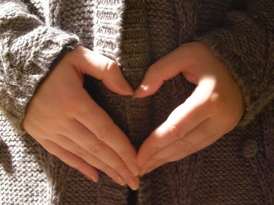 Image: the hands of someone wearing a sweater form the shape of a heart